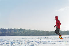 Trail racing runner wearing red protective sportswear on winter training session outdoors Stock Images