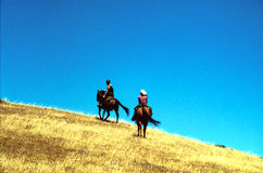 Trail ride to the sky. 2 riders enjoy a ride up a grassy mountain royalty free stock photography