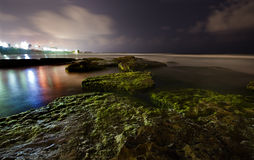 A trail of rocks in the ocean and city lights. Deserted beach, moss covered rocks and city lights, at night, horizontal Royalty Free Stock Images