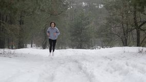 Trail Run. Young Attractive Caucasian girls running in the forest on the snow. Front static shot stock video footage
