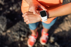 Trail runner athlete using smart watch cardio app. Trail runner athlete using her smart watch app to monitor fitness progress or heart rate during run cardio Stock Image