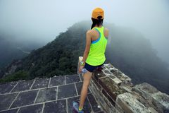 Trail runner haves a rest at great wall on the top of mountain. Woman trail runner haves a rest at great wall on the top of mountain Royalty Free Stock Photos