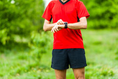 Trail runner looking at sport watch Stock Photo