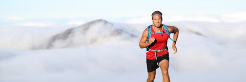 Trail runner man athlete running in mountains. Outdoor nature with mountain peak in clouds in background. Panorama horizontal banner landscape crop for stock photography