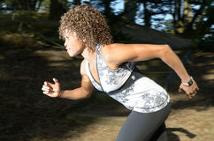 Trail running. African American woman running through a woodland Stock Image