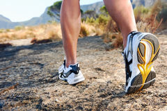 Man feet running. Trail running athlete feet on rock excercising fitness and healthy lifestyle Stock Image