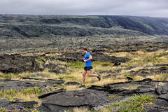 Trail Running fitness male ultra runner in nature. Landscape, volcanic rocks. Sport running man in cross country trail run. Male athlete exercising and training stock image