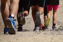 Trail running group on mountain path. Exercising,freeze action closeup of running shoes in action royalty free stock images