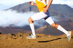 Trail running - male runner in cross country run. Closeup of strong legs and running shoes sprinting at speed. Male athlete fitness runner in compression Royalty Free Stock Images