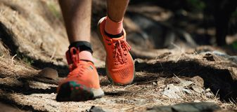 Trail running man on mountain path. Exercising,freeze action closeup of running shoes in action stock image