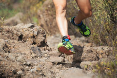 Trail running man on mountain path exercising. Workout outdoors on rocky terrain Stock Images