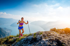 Trail running in the mountains girl athlete. Trail running in the mountains athlete girl with sticks stock image