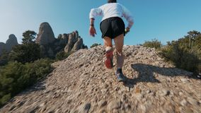 Trail running in mountains. Low angle slow motion action sports shot of strong and muscular man in sports outfit run up steep rock or cliff during ultra marathon stock video footage