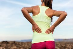Trail running runner with lower back pain. Trail running runner with painful lower back pain injury or strained muscle near the spine. Female athlete from behind stock photos