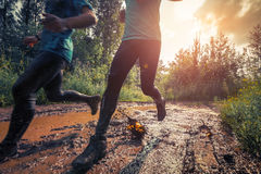 Trail running. Two trail running athletes crossing the dirty puddle Royalty Free Stock Image
