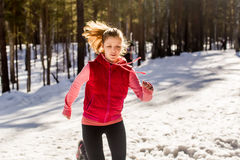 Trail running in winter. Woman fitness sport runner training outside cold winter forest path Royalty Free Stock Photo