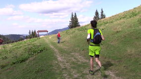Trail running. Young man running on a mountain trail and woman tourist stock video footage