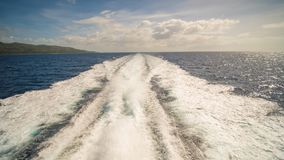 A trail of sea water foam follows the ferry to the island of Palawan. Philippines. Shooting in motion. Royalty Free Stock Image