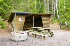 Trail shelter in Tyresta National Park, Sweden. Open log camp shelter with fireplace in Tyresta National Park, Sweden Stock Photos