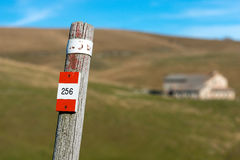 Trail Sign on a Wooden Pole - Italian Alps. Wooden pole with red and white trail sign number 256 in the Regional Natural Park of Lessinia, Veneto, Verona, Italy Royalty Free Stock Photo