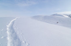 Trail in the snow in the mountains Stock Photography