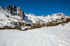 Trail through snow in the North Fork of Big Pine Creek headed toward Temple Crag on the left and North Palisade in the distance. Hiking trail and skiing skin stock photos