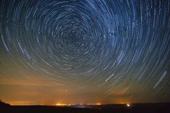Trail stars around Polar Star  glowing over city. Stock Photos