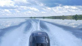 Trail on water surface behind of fast moving motor boat. the motor of motor boat, back view. Sea water ship trail with stock images