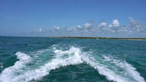 Trail on water surface behind of fast moving motor catamaran in the Caribbean Sea Cancun Mexico. Summer sunny day, blue. Sky with clouds stock video footage