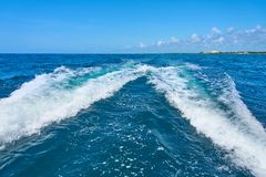 Trail on water surface behind of fast moving motor catamaran in the Caribbean Sea Cancun Mexico. Summer sunny day, blue stock photo