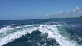 Trail on water surface behind of fast moving motor catamaran in the Caribbean Sea Cancun Mexico. Summer sunny day, blue. Sky with clouds stock video