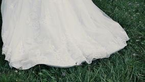 Trail wedding dress. Bride walk on the grass. In slow motion stock video