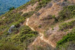 A trail winds around a mountain from lower right corner to upper left. In mid day royalty free stock image