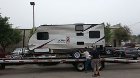A trailer being off-loaded at camping world, fort myers. A camper being carefully deposited from the back of a trailer in florida stock footage
