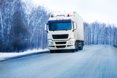 Trailer goes on the winter road Royalty Free Stock Images
