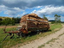 A trailer with hay. On the background there are trees, dirt road, a summer scene Stock Images