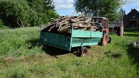 Trailer log full drive. Tractor with trailer loaded with tree wood firewood logs drive near forest stock video