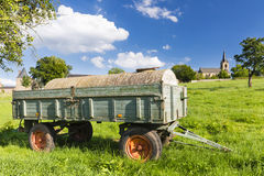 Trailer On Meadow And Village Stock Photo