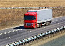 Trailer with red awning moves on the highway Stock Photo