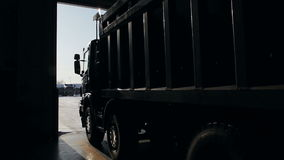 Trailer truck arrives at the service center. Lorry with trailer in service center or loading for the transport of goods. Modern dock gate closed. Freight traffic stock video footage