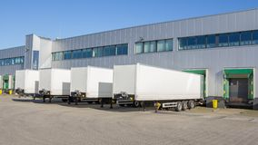 Trailers at docking stations of a distribution centre. White trailers waiting to be loaded at a docking station of a distribution centre royalty free stock images