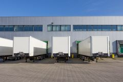 Trailers at docking stations of a distribution centre. White trailers waiting to be loaded at a docking station of a distribution centre royalty free stock photo