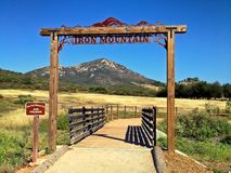 Trailhead sign post frames mountain peak in the distance Royalty Free Stock Image