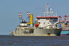 Trailing suction hopper dredger in the Weser estuary with container vessel and port facilities in the background Stock Photography