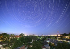 Trails of stars in night sky. Above city Stock Photo