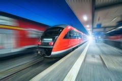 Train à grande vitesse dans le mouvement sur la gare ferroviaire la nuit Photo libre de droits