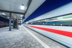 Train à grande vitesse dans le mouvement sur la gare ferroviaire la nuit Images libres de droits