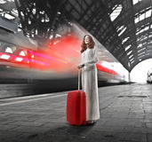 Train. Woman in white standing with her red trolley near a leaving train Royalty Free Stock Photo