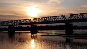 Train across the river at sunset. A train on a railway bridge over the river away from the sunset stock video footage