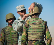 Train and Advise. US Army Combat Advisor Sergeant teaching a soldier in the Afghan National Army how to wear his helmet stock image